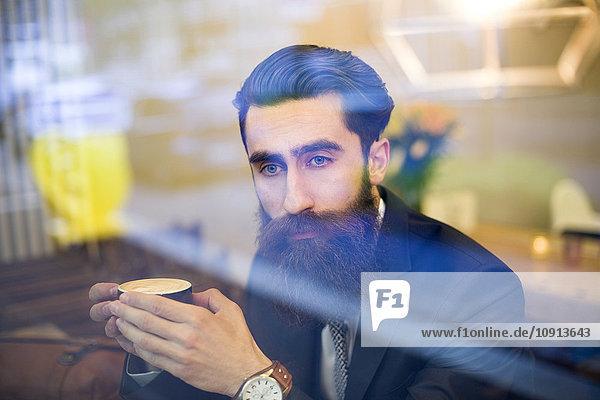 Modischer Mann mit Bart im Café sitzend, Kaffee trinkend