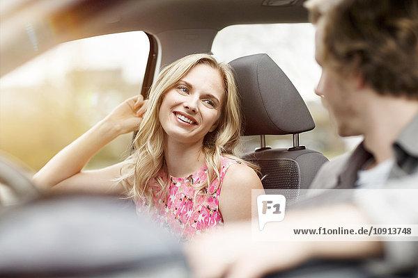 Porträt einer lächelnden blonden Frau  die auf einem Beifahrersitz im Auto sitzt und mit ihrer Freundin spricht.