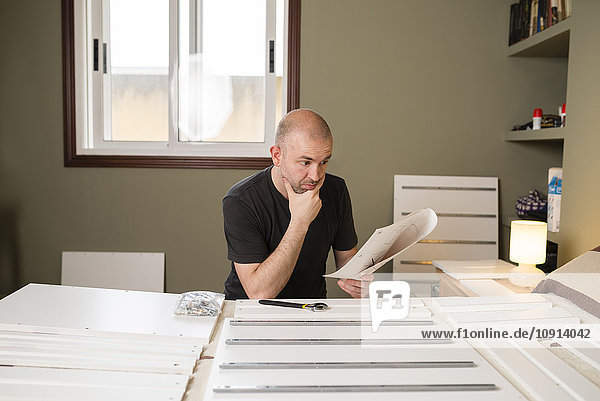 Man assembling furniture at home  reading instructions