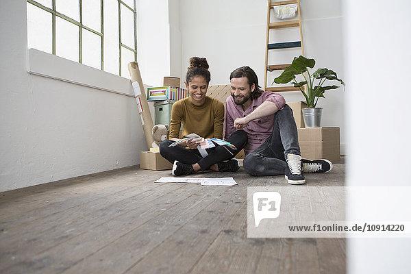 Paar sitzt auf dem Boden der neuen Wohnung und wählt aus Farbmustern aus