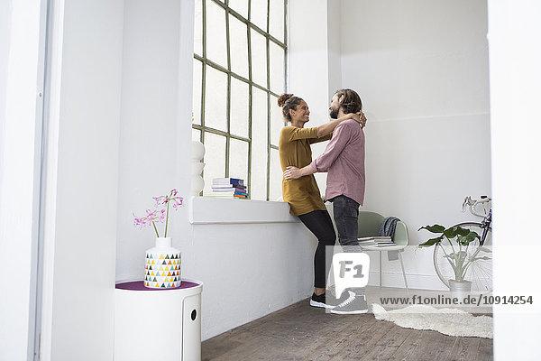 Junges Paar umarmt neue Wohnung