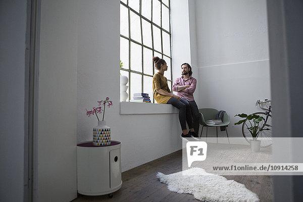 Junges Paar  das in der Wohnung sitzt und miteinander redet.