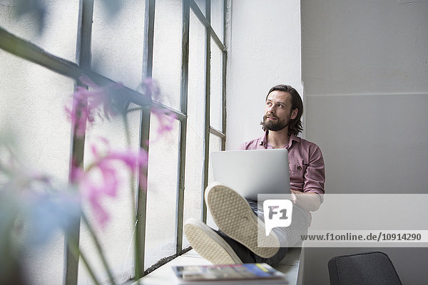 Mann sitzt auf Fensterbank mit Laptop
