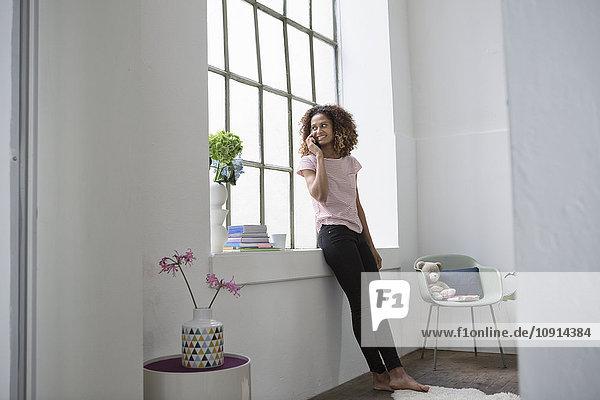 Junge Frau steht am Fenster und telefoniert.