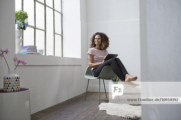 Woman sitting in chair using digital tablet