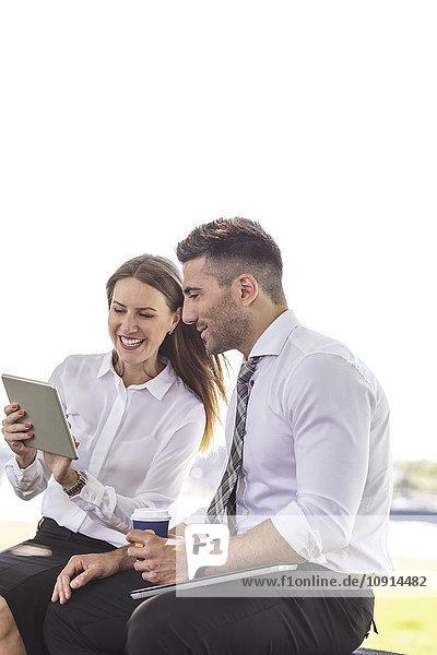 Geschäftsmann und Geschäftsfrau mit digitalem Tablett im Freien