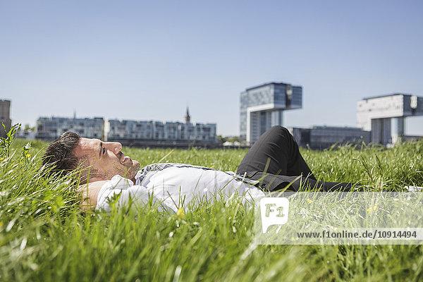 Deutschland  Köln  lächelnder Geschäftsmann auf der Wiese liegend