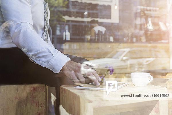 Geschäftsmann mit digitalem Tablett im Cafe