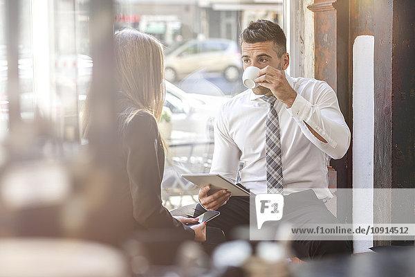 Geschäftsmann und Geschäftsfrau mit digitalem Tablett und Smartphone im Cafe
