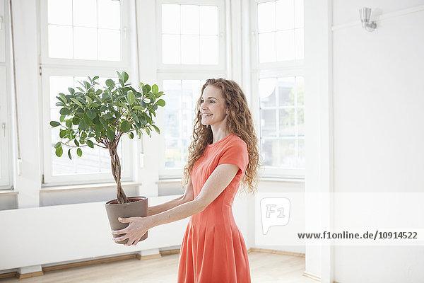 Lächelnde Frau hält Pflanze in leerer Wohnung