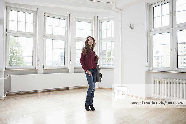 Woman looking around in empty apartment