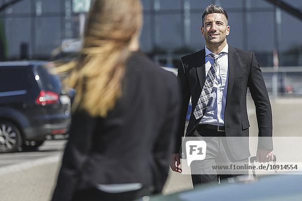 Lächelnder Geschäftsmann mit Gepäck auf dem Parkplatz mit Blick auf die Frau