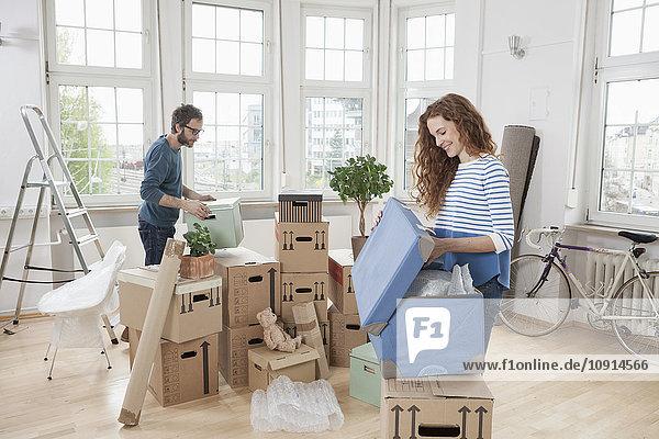 Paar in neuer Wohnung Auspacken von Kartons