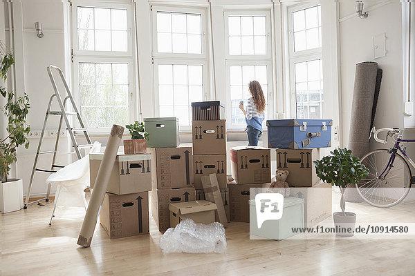 Frau mit Pappkartons in neuer Wohnung mit Blick aus dem Fenster Frau mit Pappkartons in neuer Wohnung mit Blick aus dem Fenster