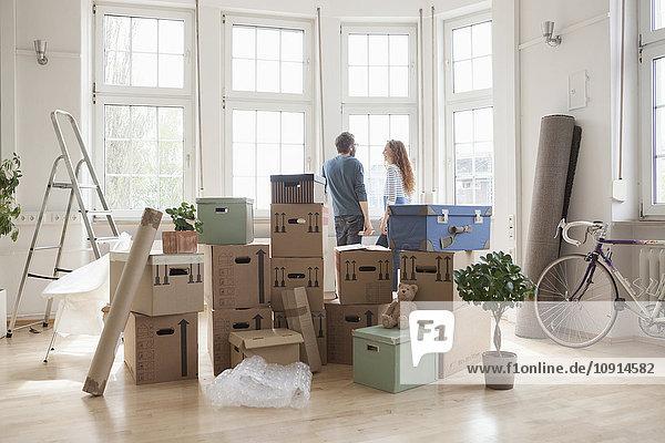 Paar mit Kartons in neuer Wohnung am Fenster