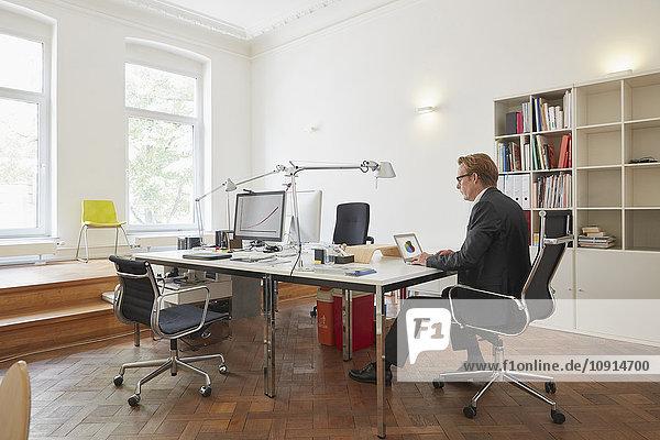Geschäftsmann bei der Arbeit mit dem Notebook im Büro