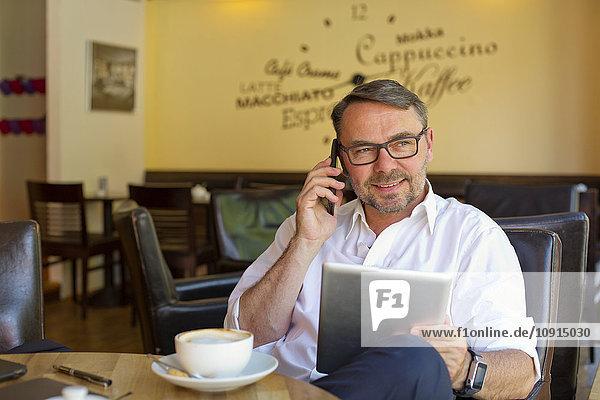 Porträt eines lächelnden Geschäftsmannes mit digitalem Tablett im Café beim Telefonieren mit Smartphone