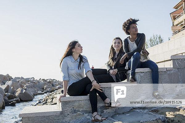 Drei junge Frauen sitzen an der Wand am Meer.