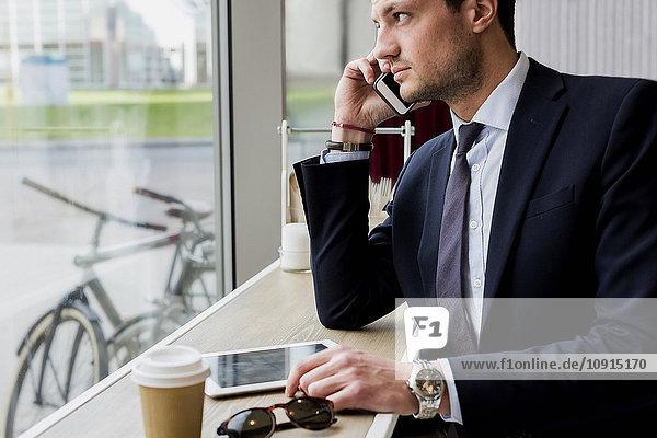 Geschäftsmann in einem Café am Handy