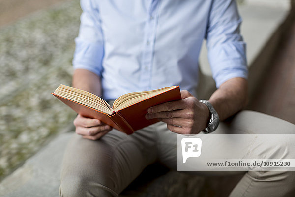 Man sitting outdoors reading book