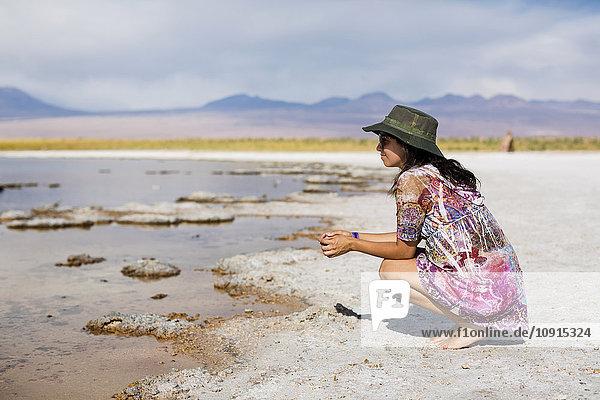 Chile  San Pedro de Atacama  Frau in der Wüste am Seeufer kauernd