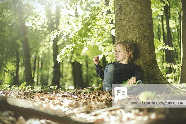 Mädchen im Wald untersucht Blätter