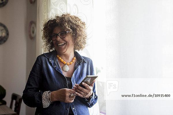 Lachende Frau hält Phablette am Fenster