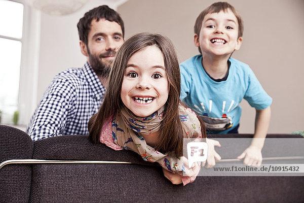 Porträt des grinsenden kleinen Mädchens zu Hause mit Vater und Bruder im Hintergrund
