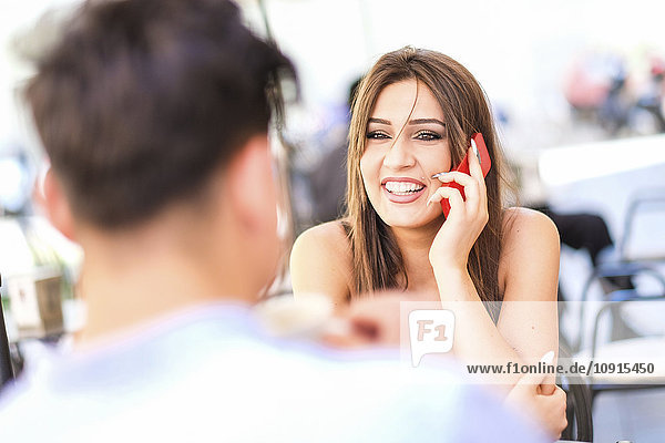 Portrait of happy young woman talking on the phone while looking at her boyfriend