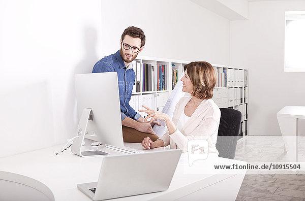 Zwei Kollegen diskutieren ihre Arbeit in einem Büro