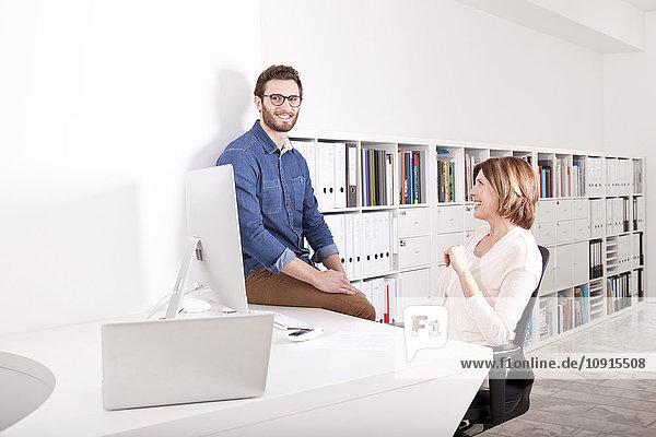 Zwei lächelnde Kollegen in einem Büro