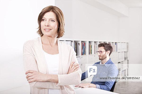 Porträt einer Frau im Büro mit Arbeitskollegin im Hintergrund