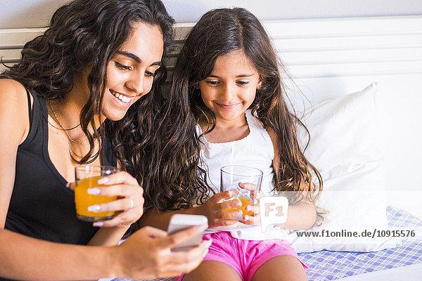 Lächelndes Teenagermädchen und ihre kleine Schwester mit Saftbrille und Handy