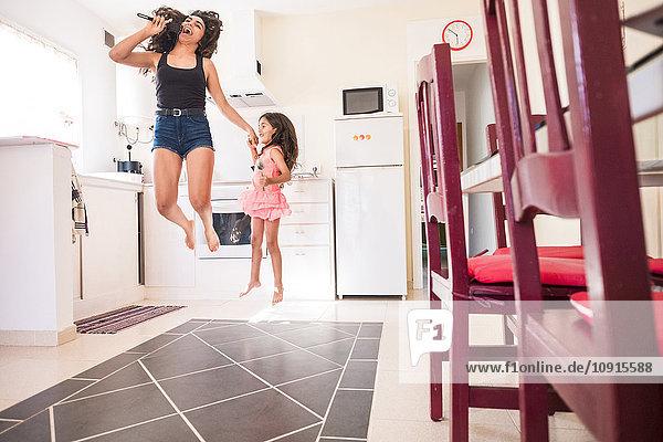 Verspieltes Teenagermädchen mit ihrer kleinen Schwester in der Küche  die vorgibt  ins Mikrofon zu singen.