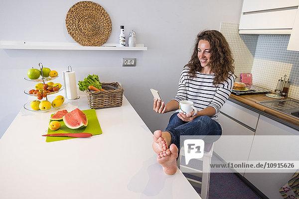 Lächelnde Frau sitzt mit erhobenen Füßen in der Küche und schaut auf das Handy.