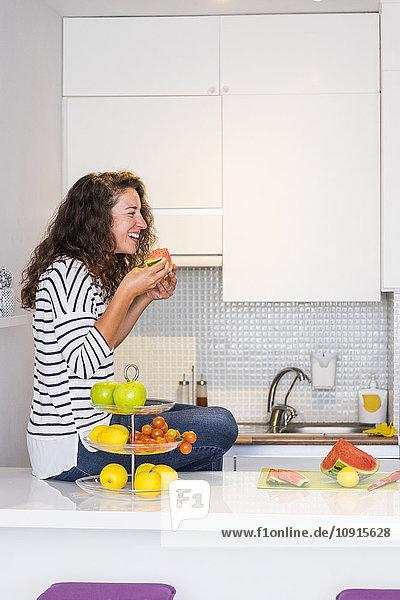 Lachende Frau sitzt auf der Küchenarbeitsplatte und isst Wassermelone.