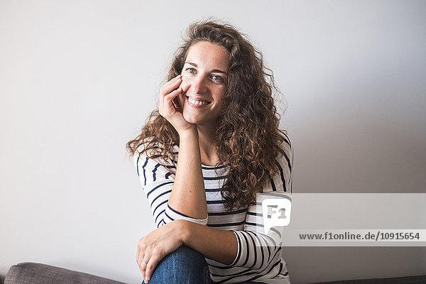 Junge Frau zu Hause sitzend mit der Hand am Kinn