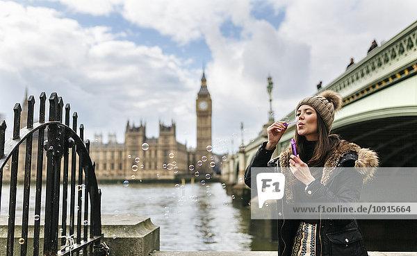 UK  London  young woman blowing soap bubbles