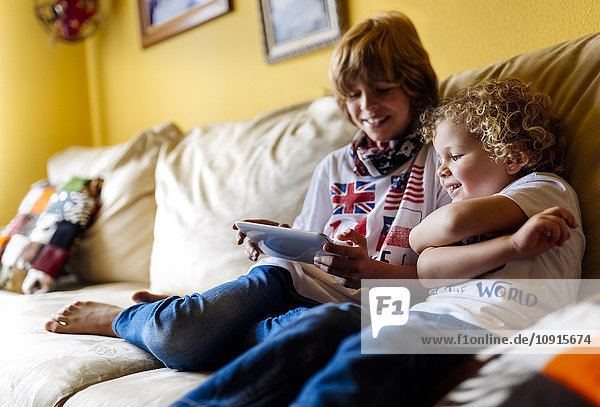 Two boys sitting on couch using digital tablet