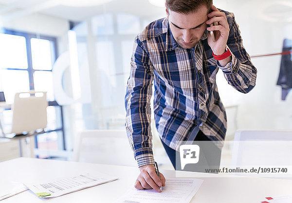Junger Mann im Amt am Telefon schreibt auf Papier