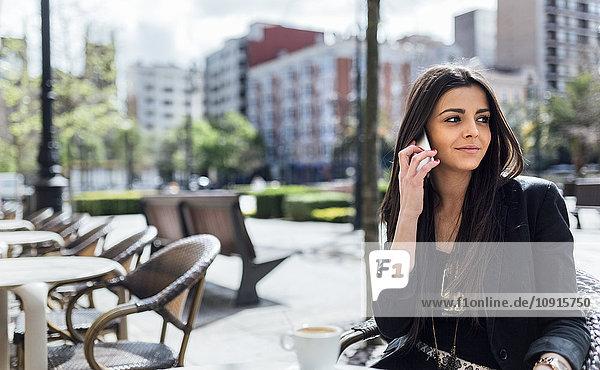 Junge Frau mit Smartphone beim Kaffeetrinken