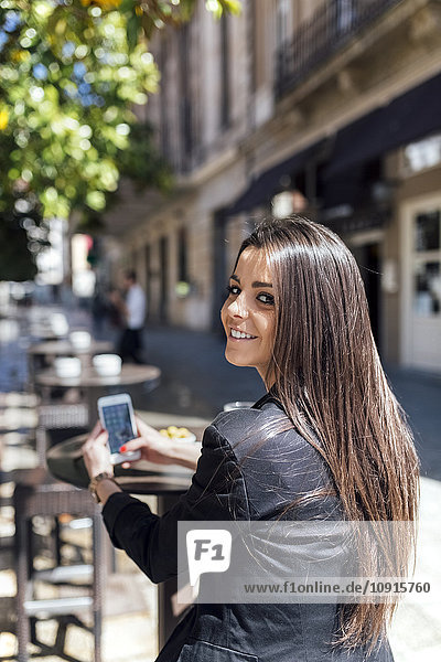 Young beautiful woman with smartphone  pavement cafe