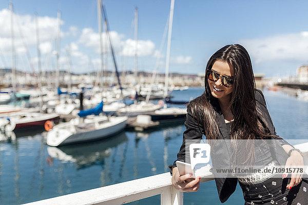 Junge Frau mit Smartphone im Yachthafen