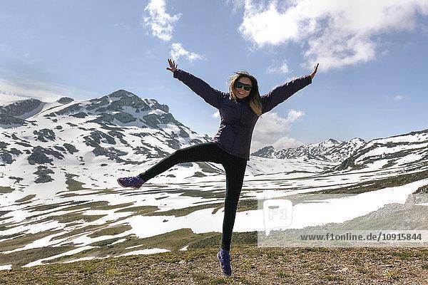 Spanien,  Asturien,  Somiedo,  verspielte Frau beim Springen in den Bergen
