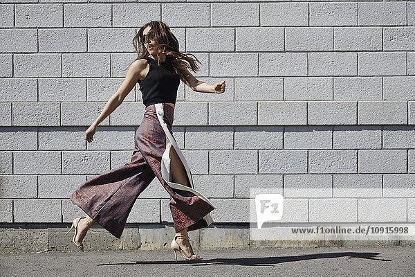 Modische junge Frau,  die an einer Ziegelmauer vorbeigeht