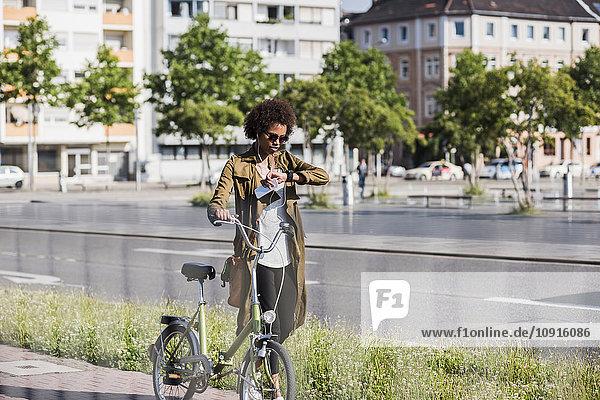 Junge Frau mit Fahrrad und Zeitkontrolle