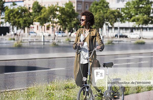 Junge Frau mit Smartphone und Kopfhörer schiebt Fahrrad
