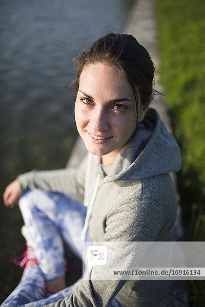 Porträt einer lächelnden jungen Frau am Seeufer