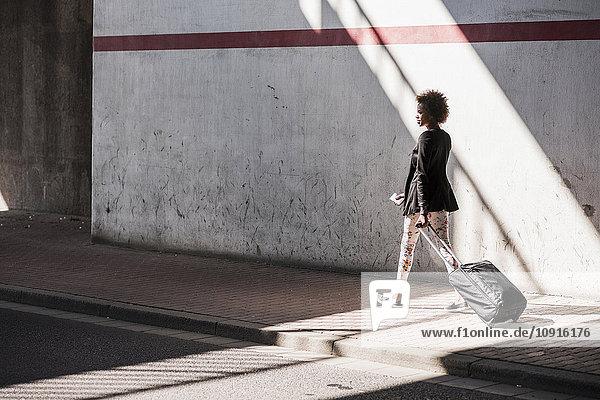 Geschäftsfrau mit Gepäck und Smartphone  die die Straße entlang läuft