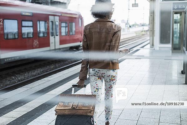 Rückansicht der jungen Frau mit Trolleytasche und Aktentasche am Bahnsteig